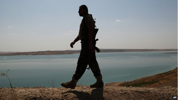 A Kurdish peshmerga fighter patrols near the Mosul Dam at the town of Chamibarakat outside Mosul, Iraq, on 17 August 2014.