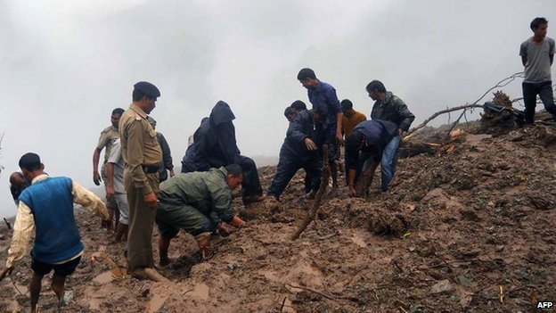 Indian residents and security personnel dig through mud following heavy rainfall and landslides in the Pauri district of the state of Uttarakhand on August 15, 2014