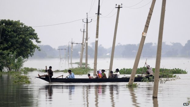 Indian villagers paddle a boat through floodwaters over submerged roads in Balimukh village in the Morigaon district of Assam state on August 17, 2014