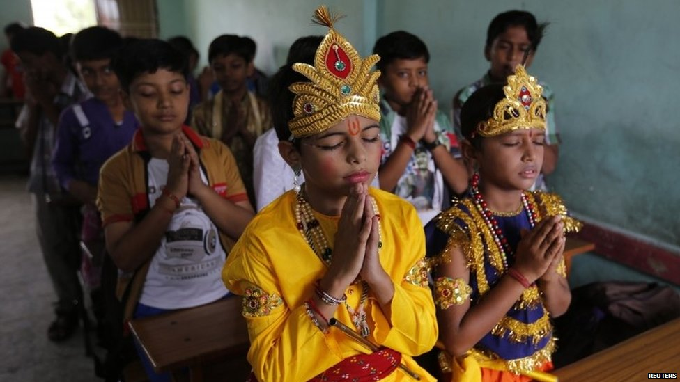 Students dressed as Hindu God Krishna (C) and his consort Radha (R) offer prayers inside their classroom during the Janmashtami festival in the western city of Ahmedabad August 16, 2014.