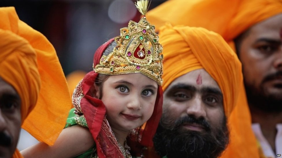 An Indian man carries a girl dressed as Radha, consort of Hindu god Krishna, during a procession on the eve of Janmashtami festival in Jammu, Saturday, Aug. 16, 2014