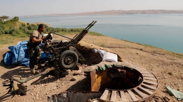 A Kurdish Peshmerga fighter prepares his weapon near the Mosul Dam at the town of Chamibarakat (17 August 2014)