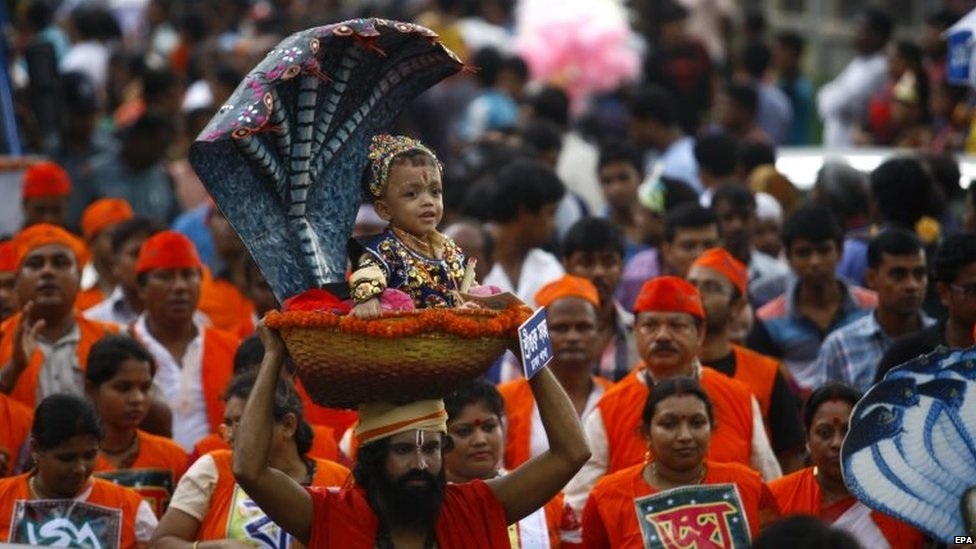 A Bangladeshi man carries a Hindu child dressed like Krishna during the celebration of Janmashtami, in Dhaka, Bangladesh, 17 August 2014.