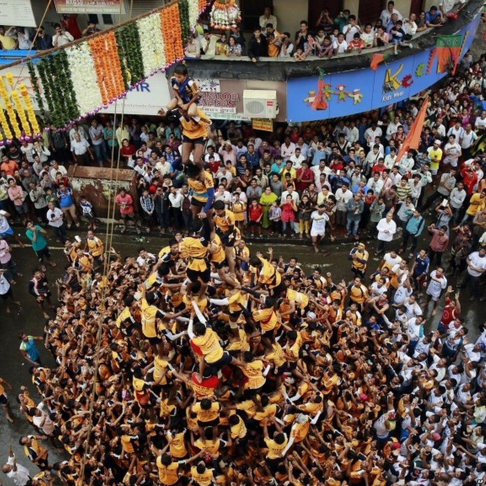 "Indian youth form a human pyramid to break the ""Dahi handi,"" an earthen pot filled with curd, an integral part of celebrations to mark Janmashtami in Mumbai, India, Monday, Aug. 18, 2014."