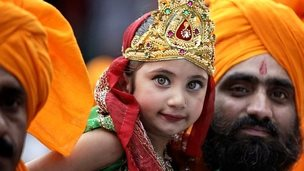 An Indian man carries a girl dressed as Radha, consort of Hindu god Krishna, during a procession on the eve of Janmashthami festival in Jammu, Saturday, Aug. 16, 2014
