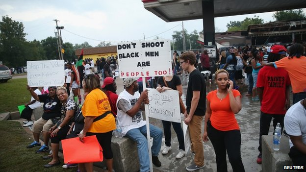 Demonstrators gesture with their hands up after protests in reaction to the shooting of Michael Brown turned violent near Ferguson, Missouri 17 August 2014