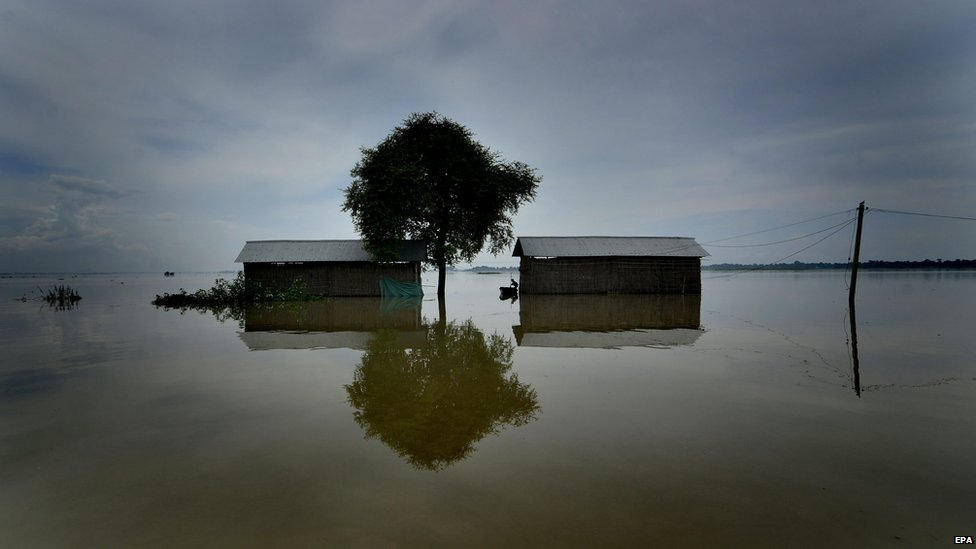 Flood waters surround some houses in an abandoned village in India, 17 August 2014.