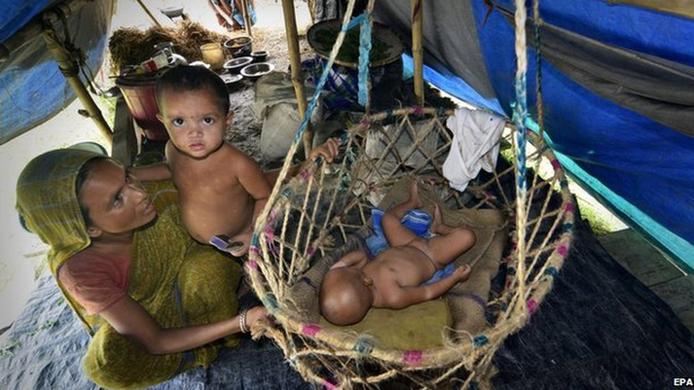 A woman keeps her babies safe in a makeshift camp in Morigaon district of Assam, 18 August 2014.