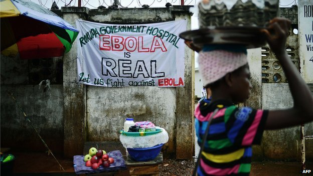 A girl walks past a sign warning of the dangers of Ebola outside a government hospital in Freetown on 13 August 2014