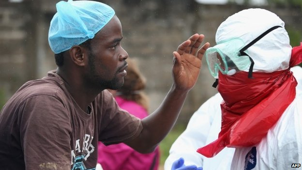 A Liberian burial team carefully puts on protective clothing before retrieving the body of an Ebola victim from his home on 17 August 2014 near Monrovia, Liberia