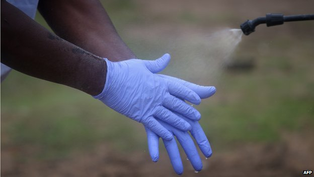 A Liberian burial team carefully disinfects their protective gloves for disposal after retrieving the body of an Ebola victim from his home on 17 August 2014 near Monrovia, Liberia