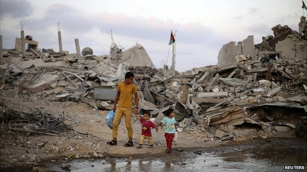 Palestinians walk next to the ruins of houses in the southern Gaza Strip - 18 August 2014
