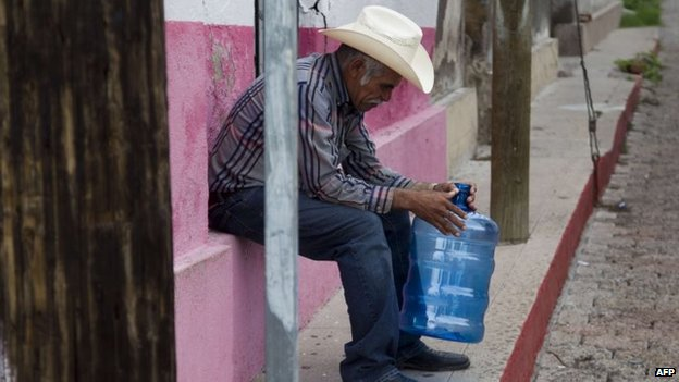 A resident waits for drinking water in the Arizpe community on 12 August, 2014