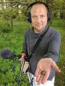 Dan in radio broadcasting gear while holding an English truffle