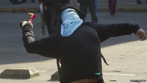 A masked protester in clashes with police in Santiago on 3 July, 2014