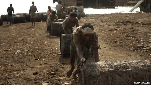 Labourers move oil barrels from a ship being scrapped in the port city of Chittagong, Bangladesh