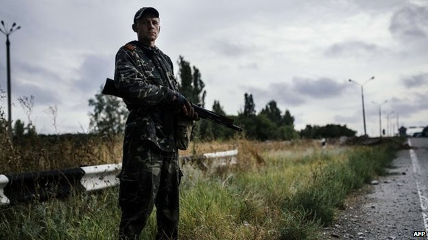 A pro-Russia militant stands guard on a road near Donetsk, 18 August 2014