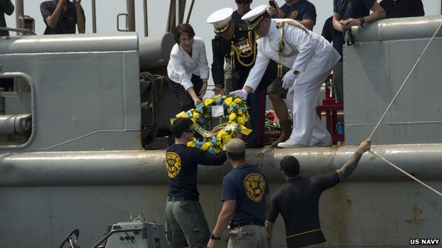 US and naval officials pass a wreath to Sailors assigned to Mobile Diving Salvage Unit (MDSU) 1 during a wreathe laying ceremony for the sunken Navy vessel USS Houston (CA 30) 12 June 2014