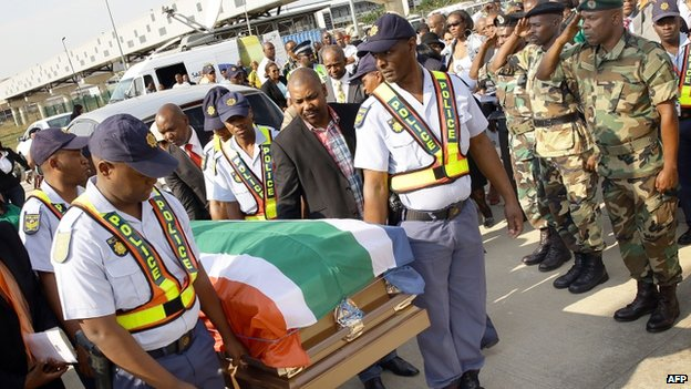 South African police carry the coffin containing the remains of anti-apartheid and former Drum magazine journalist Nat Nakasa at the King Shaka International airport on 19 August 2014 in Durban, South Africa