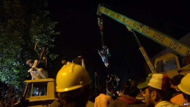 Supporters of Canada-based preacher Tahir-ul-Qadri climb on a crane to remove containers to march towards the parliament as they take part in an anti-government demonstration in Islamabad, 19 August 2014