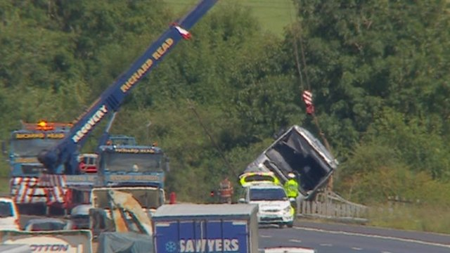 A crane lifts the coach from the ditch by the M5