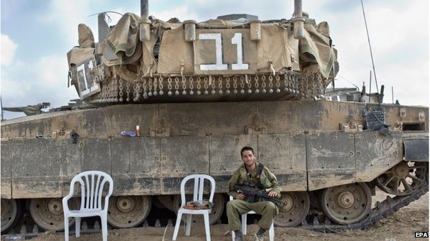 An Israeli soldier sits next to a Merkava tank in a staging area in southern Israel