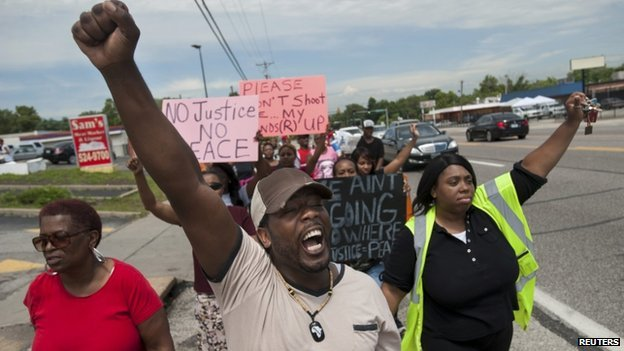 Protestors march down West Florissant Avenue in Ferguson, Missouri