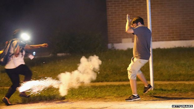Police lob tear gas at people walking near a protest over the killing of teenager Michael Brown