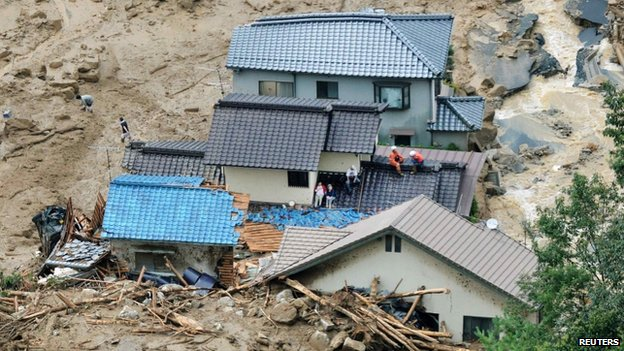 Local residents wait for rescuers on collapsed houses after a massive landslide swept through a residential area in Hiroshima, western Japan, on 20 August 2014