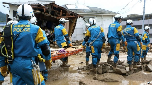 A troop of police rescue personnel head out for rescue operations after a massive landslide swept through a residential area in Hiroshima, western Japan, on 20 August 2014