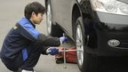 A worker at an auto shop changes the tyres on a car in Shanghai