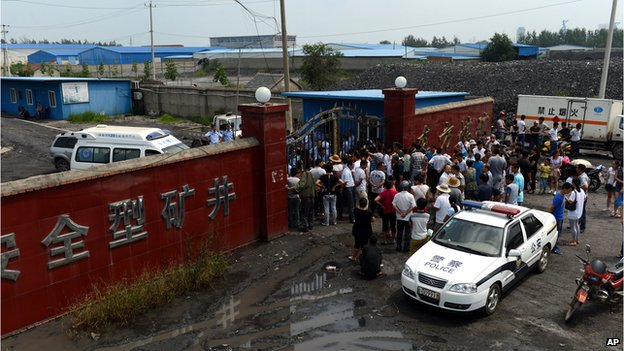 People gather outside the Dongfang Coal Mine in Huainan city, east China's Anhui Province on 19 August, 2014