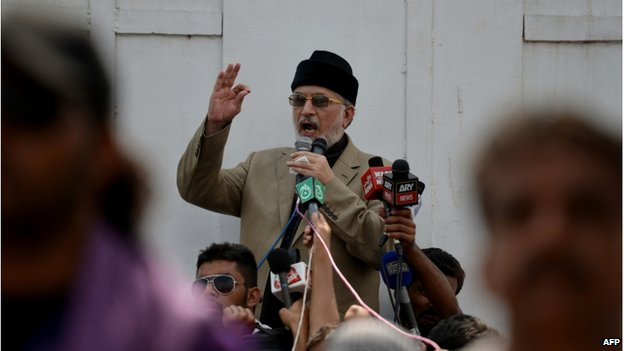 "Canada-based preacher Tahirul Qadri is surrounded by Pakistani supporters as he addresses demonstrators in front of the Parliament during the ""Revolution March"" protest in Islamabad on 20 August 2014."