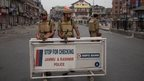 Indian policemen stand guard at a temporary check point during curfew in Srinagar, Friday, Aug. 15, 2014.