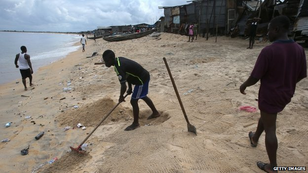 A boy rakes faeces into a hole on the beach in the West Point slum on 19 August 2014 in Monrovia, Liberia
