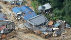 Houses are heavily damaged after a massive landslide swept through residential areas in Hiroshima, western Japan