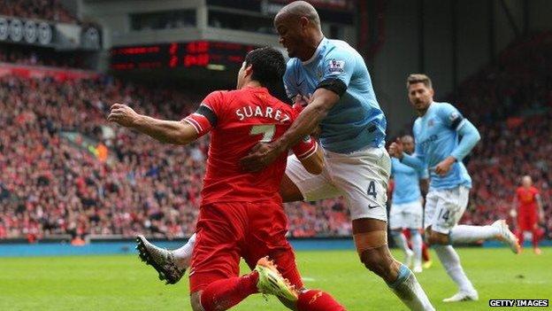 Vincent Kompany tussles with Luis Suarez