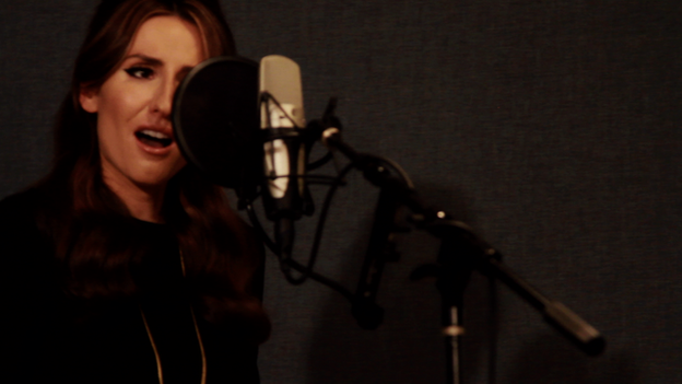 Ilse singing into a microphone in the studio