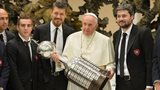 Pope Francis holds the Libertadores Cup flanked by members of San Lorenzo football team during his weekly audience on 20 August, 2014 at the Vatican