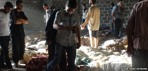 Activists inspect the bodies of men, women and children after the 21 August chemical weapons attack in Damascus