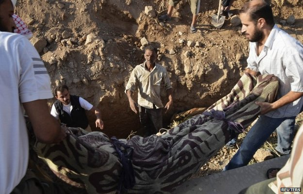 Men bury a victim of the 21 August chemical weapons attack in Damascus