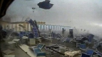 Beach chairs are lifted into the air amid a tornado