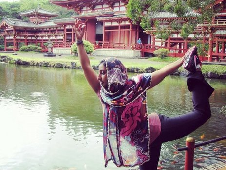 Farida Hamza doing a yoga pose near a lake