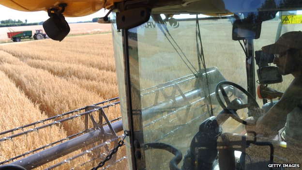 A French farmer harvests an oat field on a combined harvester using GPS