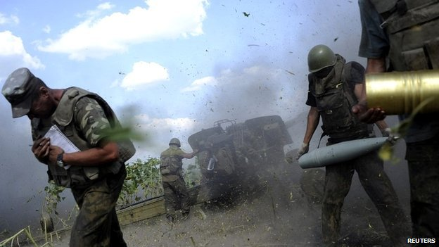 Ukrainian soldiers take cover while firing a cannon towards separatists near Pervomaisk, Luhansk - 20 August 2014