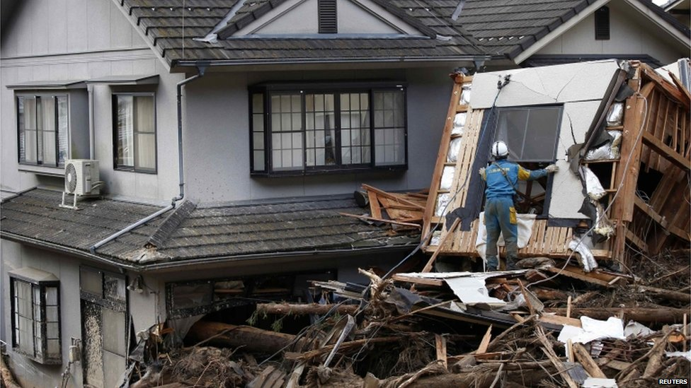 A police officer searches for survivors at a site where a landslide swept through a residential area at Asaminami ward in Hiroshima, western Japan, on 21 August, 2014