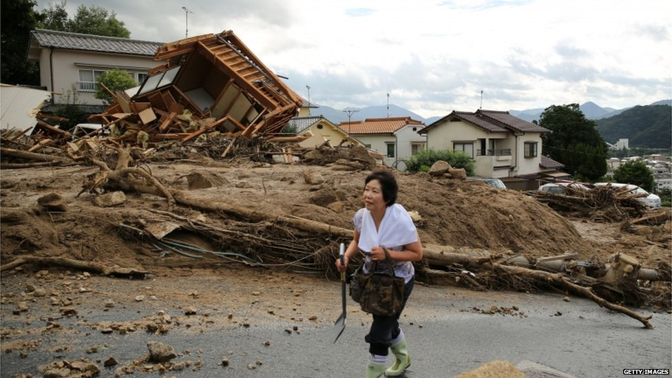 A local resident visits a landslide site to check if her house are damaged by a landslide caused by torrential rain on August 21, 2014 in Hiroshima, Japan
