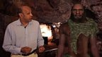 Pallab Ghoash walking next to simulation of a Neanderthal man