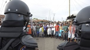 Liberian security forces stand in front of protesters after clashes at West Point neighbourhood in Monrovia August 20, 2014.