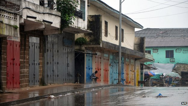 A lone man sits outside shops that were closed in Monrovia's West Point slum